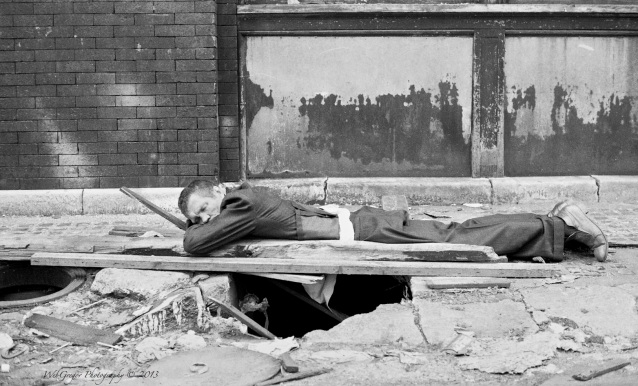Man Sleeping Outside on Sidewalk
